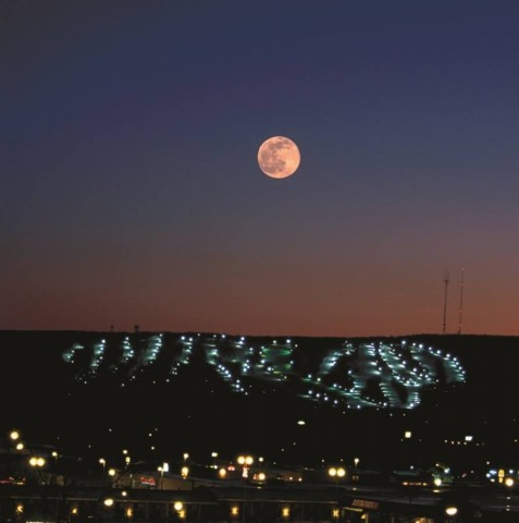 A full moon rises over Granite Peak and the city of Wausau.