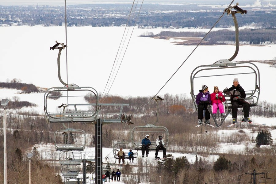 The lift carries skiers up the mountain with Lake Superior and the Duluth Harbor in the background. (Spirit Mountain)