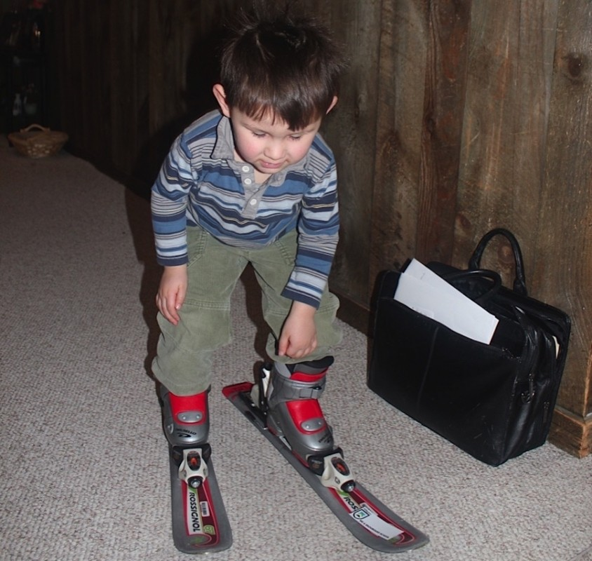 Toddler adjusts to boots and skis in house as advised by children's program director. KL photo