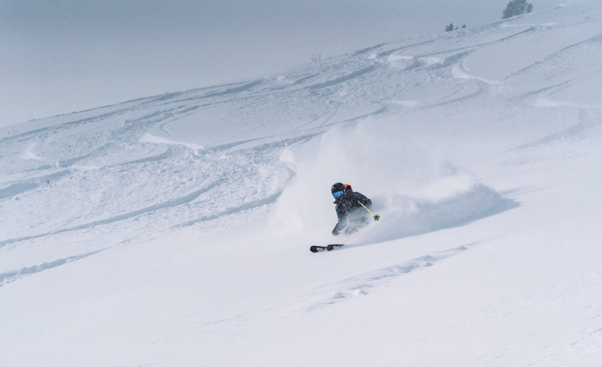 Skier gliding down trail of snow at Snowbasin Resort in utah